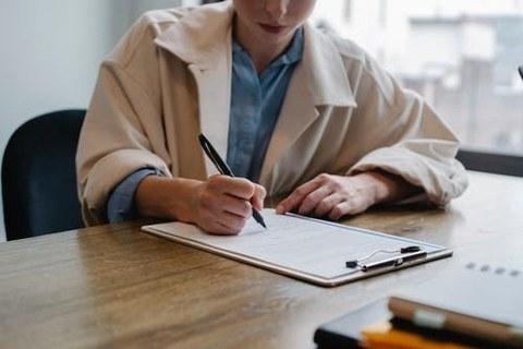 Mädchen füllt Formular aus, sitzend am Tisch