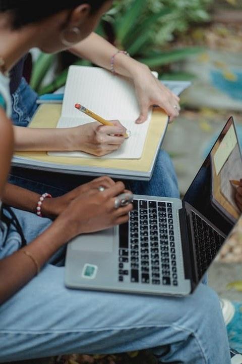 zwei Personen nebeneinander sitzend mit Zetteln und Laptop
