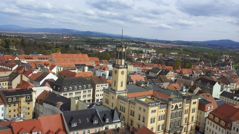 Foto mit Blick auf die Stadt Zittau von einem Kirchturm aus. Im Mittelpunkt des Bildes ist das Zittauer Rathaus zu sehen.