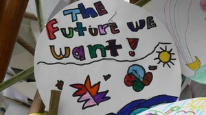 "Photo with a circular white picture, which is colorfully painted. In the upper half is written in different coloured letters ""The future we want""."