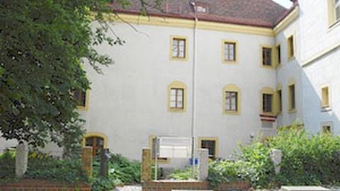 Foto des IZS in Görlitz. Zeigt den Hof mit Gebäudefassade, Baum am linken Rand und Weg am unteren Rand des Bildes.