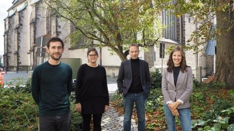 Vier Menschen stehen nebeneinander auf einem Hof. Im Hintergrund Bäume und eine Kirche