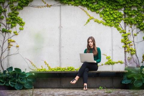 Studentin sitzt im Freien mit einem Laptop und liest