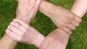 Vier Hände greifen ineinander