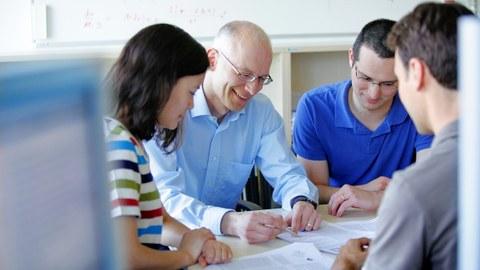 drei junge Absolventen und ein älterer Gruppenleiter sitzen während einer lebhaften Diskussion an einem Tisch