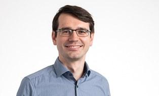 Mann mit kurzen dunklen Haaren, Brille und grauem Hemd