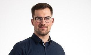 Mann mit kurzen dunklen Haaren, Brille, Bart und dunklem Hemd