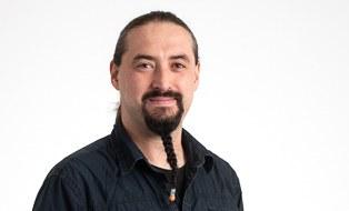 Mann mit langen dunklem Haaren im Zopf und langem geflochtenen Kinnbart