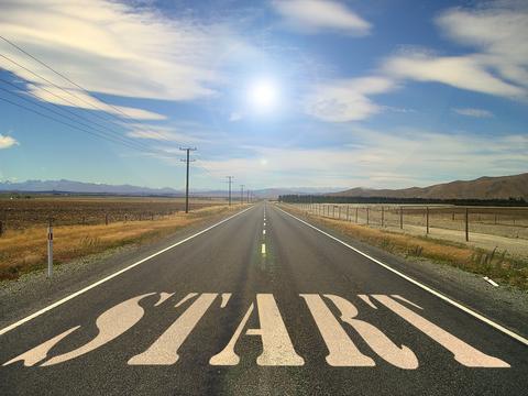 """Bild: eine weite, gerade Straße mit einem weißen Schriftzug auf Asphalt der lautet """"Start"""""""