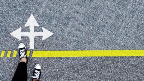 Foto: man sieht Füße einer Person, die vor einem Pfeil-Wegweiser auf Asphalt steht.