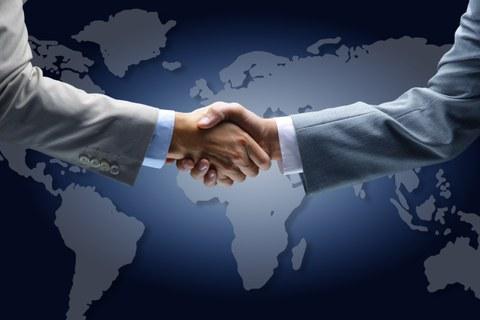 Illustration der Weltkarte im Hintergrund. Davor begrüßen sich zwei Männer mit einem Händedruck.