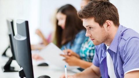Bild: Junge Menschen sitzen vor Computern. Im Vordergrund ein junger Man, der Notizen davon macht, was er vermutlich auf dem Bildschirm sieht.