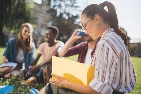 Bild: vier junge Menschen sitzen auf einer Wiese. Eine junge Frau im Vordergrund schaut in ihre Unterlagen rein