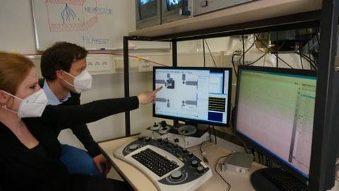 Melanie Herzig (NaMLab) und Christian Bruchatz (MemrisTec Koordination) begutachten eine ferromagnetische Memristor-Schaltung
