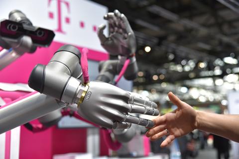 Mensch Roboter Interaktion: ein Roboter reicht die Hand einem Menschen.