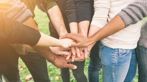 Bild: eine Gruppe der Menschen legt ihre Hände aufeinander, nur die Körper sind sichbar, Hände sind im Vordergrund