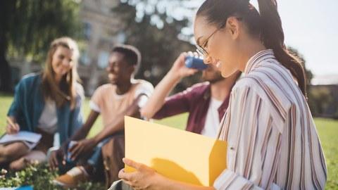 Bild: vier junge Menschen sitzen auf einer Wiese, eine junge Frau im Vordergrund schaut in ihre Unterlagen rein