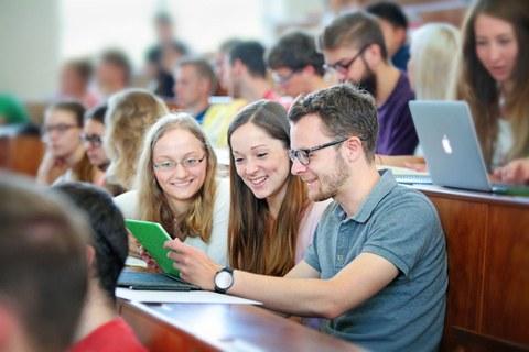 Bild: junge Menschen sitzen im Hörsaal, lächeln und schauen sich gemeinsam Unterlagen an