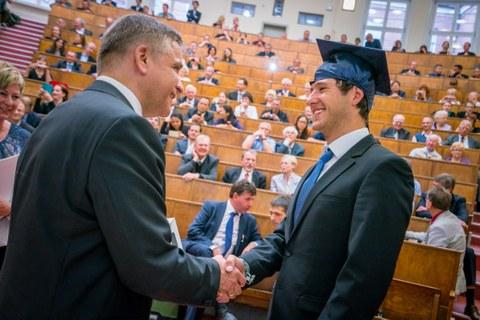 Bild: Szene vom Tag der Fakultät 2016, Dekan druckt die Hand eines jungen Mannes im Absolventenhut und gratuliert. Im Hintergrund ein Hörsaal mit festlich angezogenen Zuhörern.