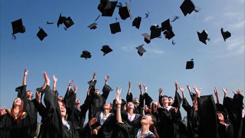 Das Foto zeigt eine Gruppe von Absolventen in langen schwarzen Mänteln. Sie werfen zeitgleich ihre Doktorhüte in die Luft und lachen dabei.