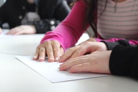 Drei Hände die eine taktile Grafik erkunden