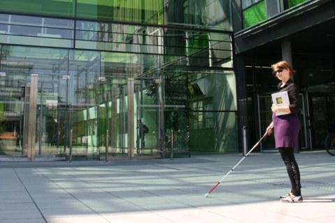 Blinde Studentin vor dem Eingang der Fakultät