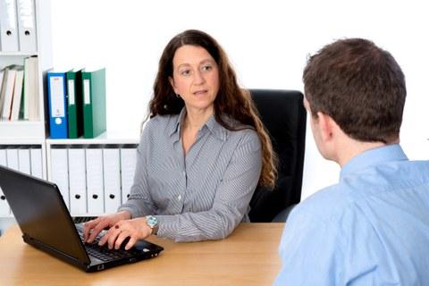 Auf dem Foto ist eine Frau am Schreibtisch an Ihrem PC zu sehen. Sie hat die Hände auf der Tastatur und unterhält sich mit einem Mann, der vor ihr sitzt.
