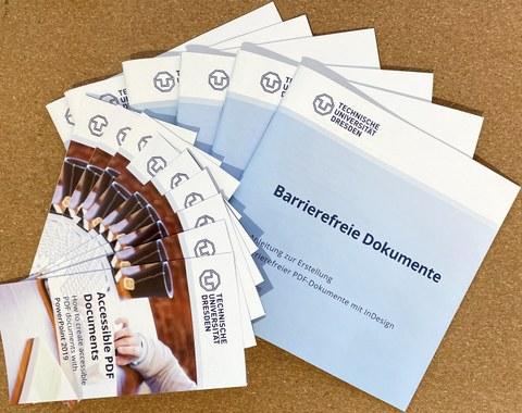 Broschüren und Flyer, aufgefächert auf dem Tisch, Anleitungen zur Erstellung barrierefreier Dokumente.