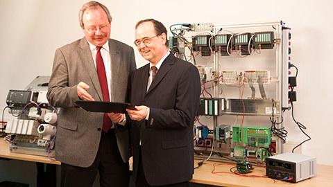 Professor Wollschlaeger und Professor Kabitzsch vor einer SPS