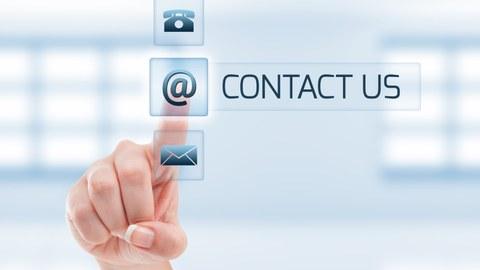 """Foto: Hellblauer Bildschirm mit drei Kontakt-Symbolen. Ein Finger tipp auf """"@"""" und daneben steht """"contact us""""."""