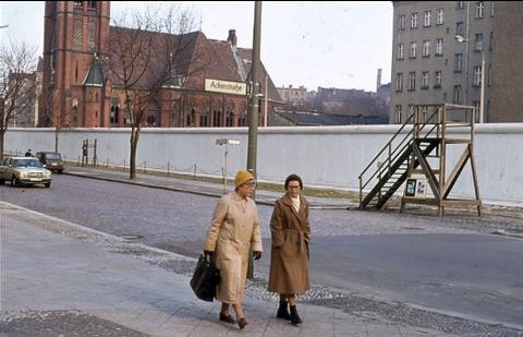 """Foto. Zwei ältere Damen in braunen Mänteln mit gestrickten Mützen laufen einen Gehweg entlang. Direkt hinter ihnen ein Straßename, """"Ackerstraße"""" an einem Laternenpfahl. Auf der anderen Straßenseite verläuft hinter dem Gehweg und einem schmalen Grünstreif"""