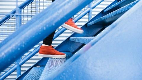 Füße mit roten Turnschuhen laufen eine Stahltreppe hinauf