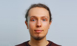 Profile photo of Tobias Hänel. He has blue eyes, dark hair tied into a bun and a short beard. He is wearing a dark red jumper.