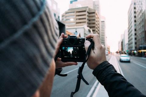 Foto eines Mannes, der mit seiner Kamera ein Foto in einer Großstadt macht.