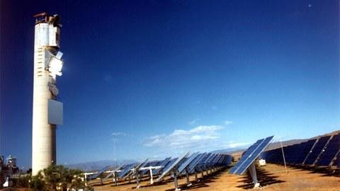 Das solare Turmkraftwerk auf der Plataforma Solar in Almería umgeben von einem Spiegelfeld, das die Solarstrahlung auf Strahlungsempfänger reflektiert. Mit der so gesammelten Wärmeenergie wird eine Turbine angetrieben, die Strom erzeugt.