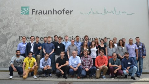 Group photo of the thirty one participants of the Summer School in front of the Fraunhofer IWS logo