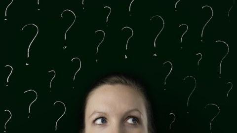 Foto mit schwarzem Hintergrund. Im Vordergrund der Kopf einer Frau umringt von weißen Fragezeichen..