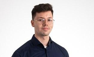 Mann mit kurzen dunklen Haaren, Brille und schwarzem Hemd