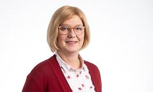 Frau mit kinnlangen blonden Haaren, Brille und heller Bluse mit roter Jacke