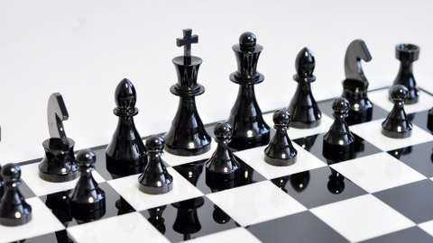 The picture focusses on the black figures of a chess set made of ceramic.