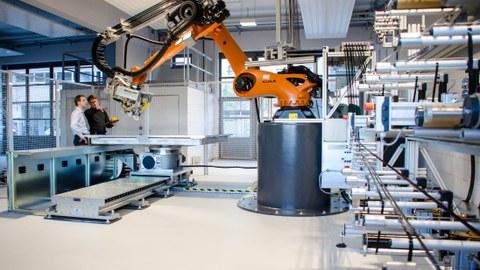 Zwei Wissenschaftler des Instituts für Leichtbau und Kunststofftechnik arbeiten an einer Tapelegeanlage..