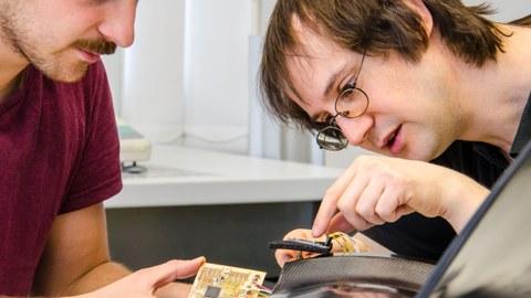 Zwei Wissenschaftler des Instituts für Leichtbau und Kunststofftechnik arbeiten den der funktionsintegierten Elektronik eines Fanbades.