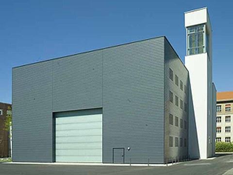 Bild einer großen grauen Werkhalle mit weißen Turm am rechten Gebäuderand.