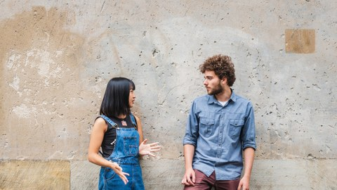 Photo: An Asian woman and a man lean against a concrete wall and talk.