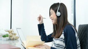 The photo shows a young woman at her desk. She is wearing headphones, smiling and writing something down in her notebook.