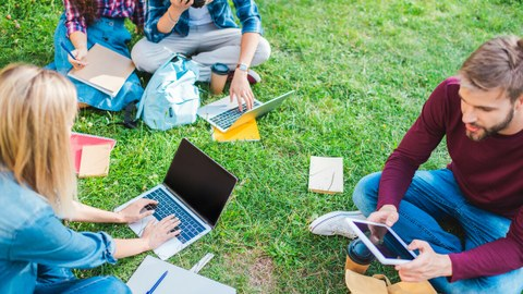 The photo shows several students. They are sitting on a lawn with their laptops and studying.