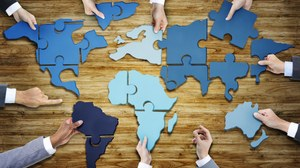 The photo shows the hands of people in business clothes. They are standing around a table. Pieces of a puzzle are lying on the table. Put together they form a map of the world.