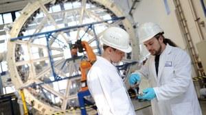 Zwei Wissenschaftler des Instituts für Leichtbau und Kunststofftechnik beraten sich von dem Flechtrad.