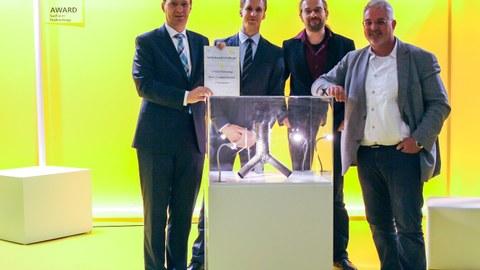 Eine Gruppe von vier Wissenschaftlern steht vor einer Messevitrine aus der Fachmesse Materialica in München.