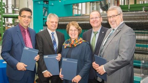 Gruppenbild vor einer Textilmaschine des ITM: Prof. Chokri Cherif (ITM), Prof. Hubert Jäger (ILK), Prof. Brigitte Voit (IPF), Prof. Alexander Michaelis (IKTS), and Prof. Eckhard Beyer (IWS) (v.l.n.r.)